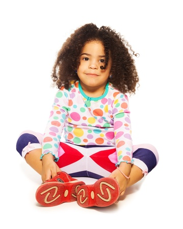 frizzy: Happy black girl sitting on the floor isolated on white with frizzy hair