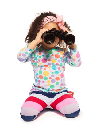 frizzy hair: Happy black girl sitting on the floor with binoculars isolated on white waiving with frizzy hair Stock Photo