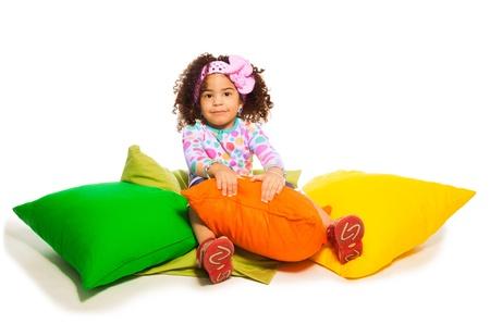 Leuke zwart krullend twee jaar oud meisje zitten in de kussens, geïsoleerd op wit