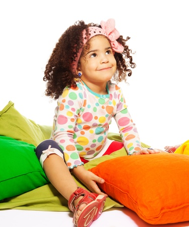 two years: Cute black curly two years old smiling girl sitting in the pillow, isolated on white Stock Photo