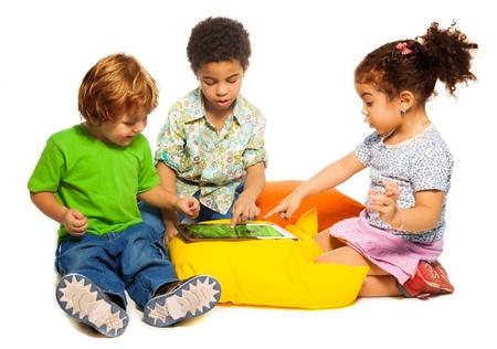 ni�os riendose: Dos diversidad busca chicos y una ni�a jugando con el ordenador tableta sentado sobre almohadas Foto de archivo