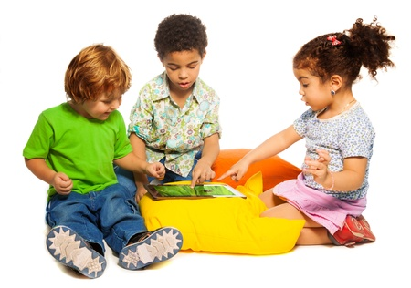 three children: Two diversity looking boys and girl playing with tablet computer sitting on pillows