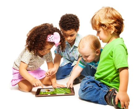 black children: Four little kids playing with tablet computer, isolated on white
