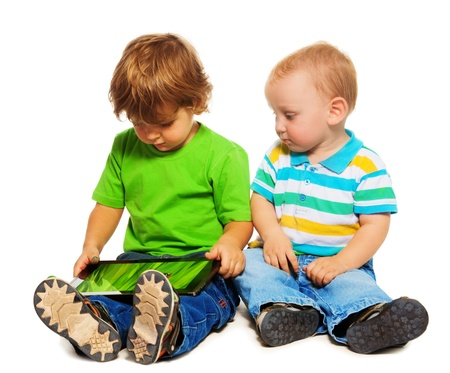 sibling: Two kids - little two years old playing with tablet computer