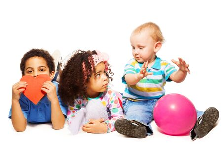 Three little kids black boy and girl and Caucasian child playing together photo