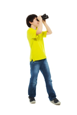 Happy boy holding binoculars and smiling, isolated on white, side view, full height photo