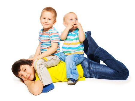 Dos hermanos más jóvenes sentados en la parte posterior del hermano mayor