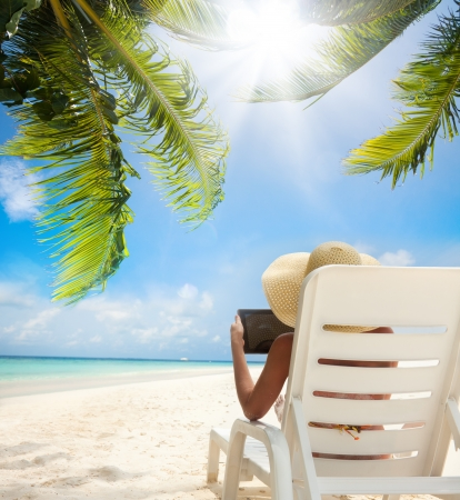 palm computer: Tropical beach and woman relaxing with tablet computer sitting on the sun chair