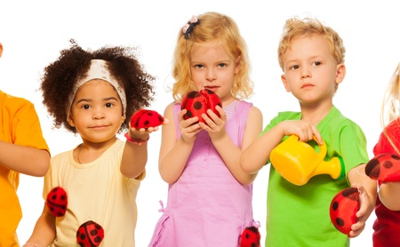 Group of kids with toy spring lady bugs and watering can