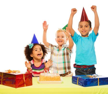 birthday party kids: Three kids celebrating birthday - two boys and girl with cake and presents on the table