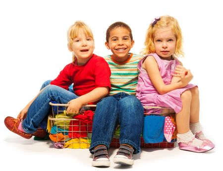 three kids sitting in the clothes basket - black boy and two blond girls Stock Photo - 18394628