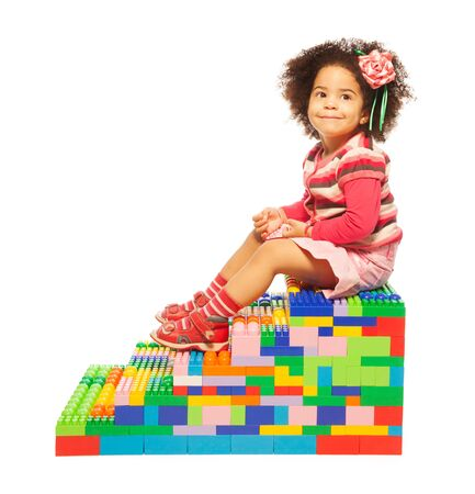 dark skinned: Dark skinned two years old girl on the stairs maid or toy plastic blocks Stock Photo
