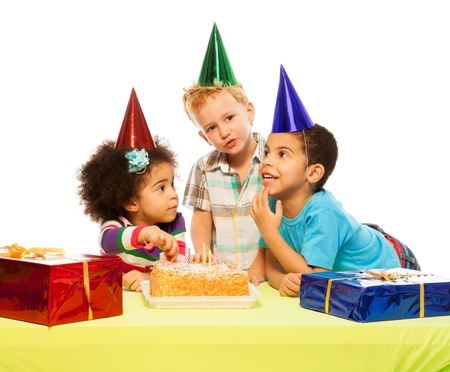 Three kids sitting by the table with presents and birthday cake photo