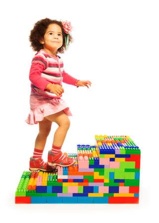 subiendo escaleras: Chica Oscuro escalada en las escaleras de juguete hechas de bloques de plástico Foto de archivo