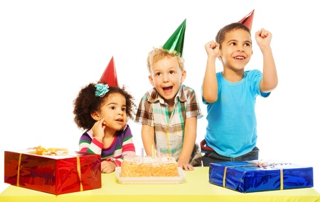 Three diversity looking kids on birthday party with presents and cake, very exited, laughing and smiling, isolated on white photo