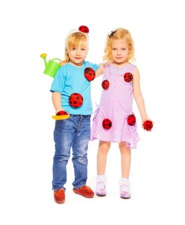 five years old: Two spring little blond girls friends standing together holding ladybugs and watering can, isolated on white