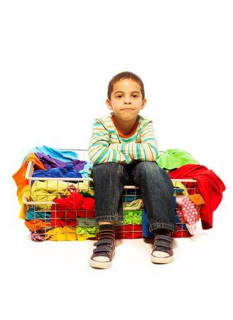 five years old: Bambino di cinque anni del ragazzo nero seduto nel carrello con abiti di moda, isolato su bianco