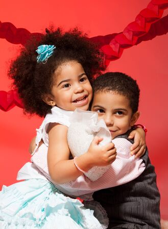 Older brother hug little sister who is holding toy heart photo
