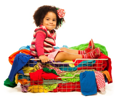 Black girl sitting in the basket with clothes isolated on white Stock Photo