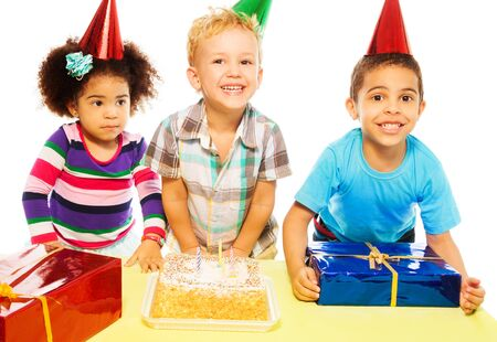 Group of three happy five years old kids with smile on the table with presents and birthday cake, isolated on white photo