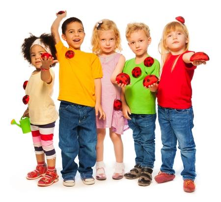 five years old: Gruppo di cinque anni i bambini con irrigazione luminoso pu� e coleotteri