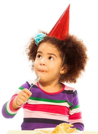 1 2 years: Cute little black three years old girl with fuzzy hair and party hat eating birthday cake with spoon isolated on white Stock Photo