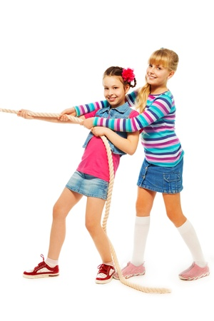Two 9-10 years old girls pulling the rope in team standing isolated on white Stock Photo - 18394588