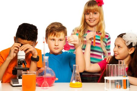 science education: Team of four kids, black and white, boys and girls experimenting on chemistry lesson with test tubes, liquids and flasks, isolated on white Stock Photo