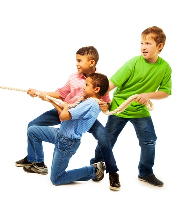 Boys team of three 8-11 years old kids pulling the rope standing isolated on white Фото со стока