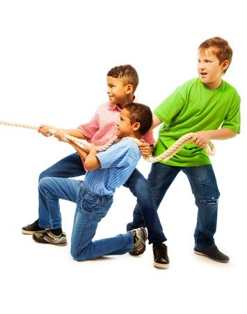 Zespół Chłopcy z trójką dzieci 8-11 lat starych ciągnąc liny stojący odizolowane na białym