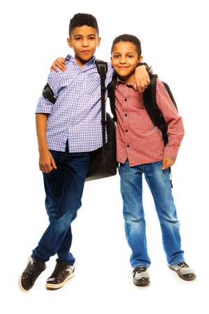full height: Two happy black brothers standing together with backpack hugging, full height portrait isolated on white Stock Photo