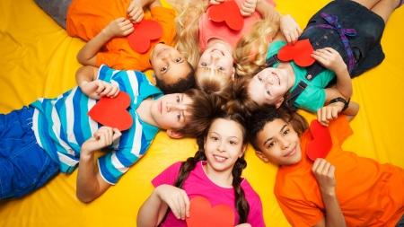 Groep van gelukkige jonge geitjes tot in cirkel op de vloer met harten in hun handen Stockfoto