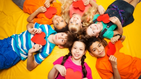 Group of happy kids laying in circle on the floor with hearts in their hands photo