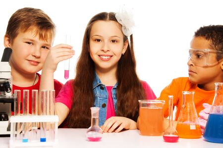 Three kids, two boys black and white and brunet girl with microscope, test tubes and flasks conducting experiments, isolated on white photo