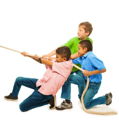 Three strong boys pulling the rope with strength standing isolated on white photo