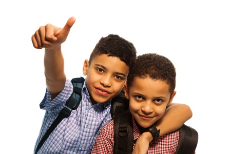 Two black boys after school with thumbs up and hugging each other