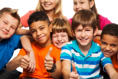 Large group of diversity happy kids boys and girls of age 8-11 years old with one of them thumbs up and smile photo