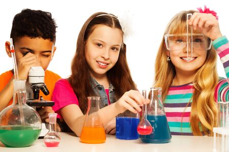 Three kids, two girls blond and brunet with test tubes and flasks conducting experiments and black boy with microscope, isolated on white photo