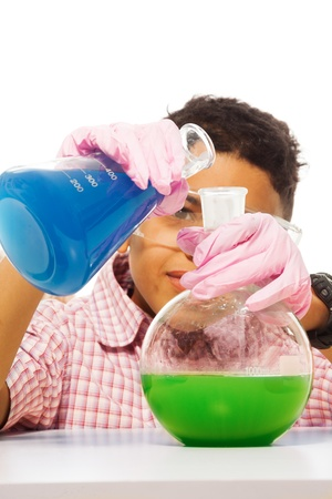 Black 10 years old boy mixing chemicals with two big flasks photo
