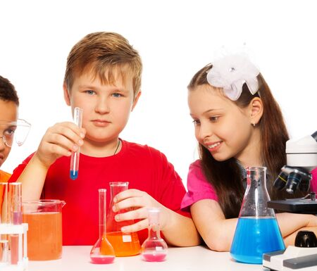 Boy and girl experimenting with chemistry mixing liquids photo