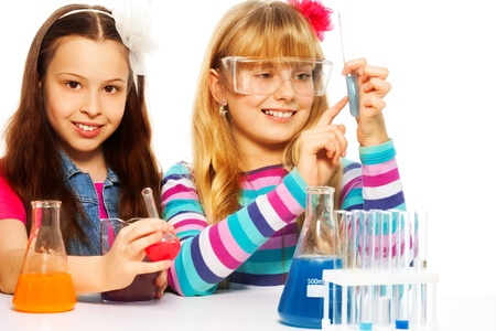 Two girls in chemistry lab class with test tubes and flasks conducting experiments, isolated on white photo