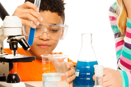 8 years old: Boy and chemistry - 8 years old mixing liquids in test tubes and flasks Stock Photo