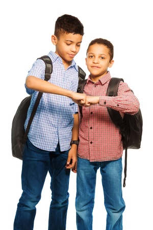 cool kids: Two happy black brothers standing together with backpack hugging, portrait isolated on white