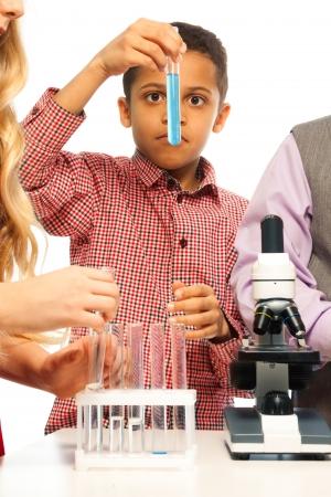 Smart black boy examining test tube on chemistry class photo