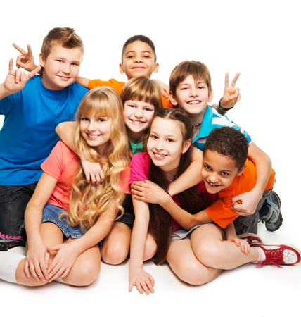 boy long hair: Group of happy smiling kids sitting together and playing - boys and girls black and Caucasian, hugging together Stock Photo