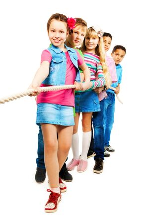 Group of five diversity looking kids, boys and girls pulling the rope together standing in a line as a team, isolated on white with brunet girl on front Stock Photo - 18394990