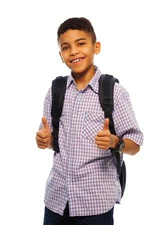 niño con mochila: Niño negro de doce años de edad sonriente con los pulgares arriba gesto y la mochila
