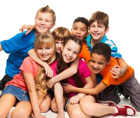 ni�os rubios: Grupo de ni�os felices sonrientes sentados juntos y jugando - muchachos y muchachas negro y del C�ucaso Foto de archivo
