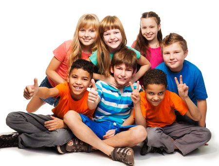 Group of happy smiling kids sitting together and playing - boys and girls black and Caucasian, isolated on white photo