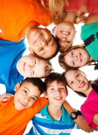 girotondo bambini: 7 ragazzi guardando gi� in piedi in un cerchio sorridente e guardando verso il basso
